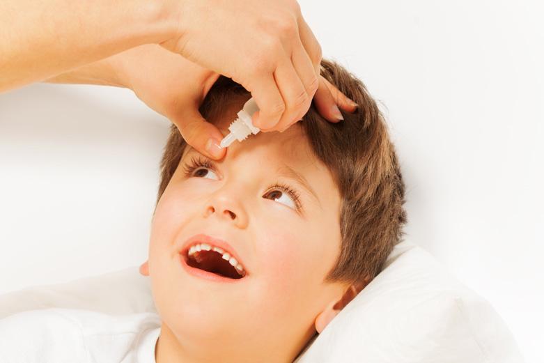 een moeder helpt haar kind oogdruppels te gebruiken